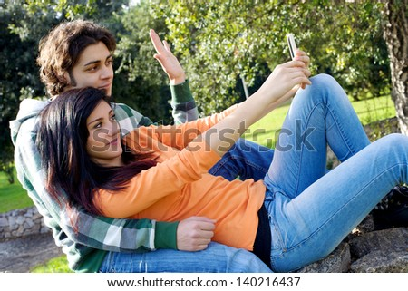 Happy couple having fun taking pictures with mobile phone - stock photo