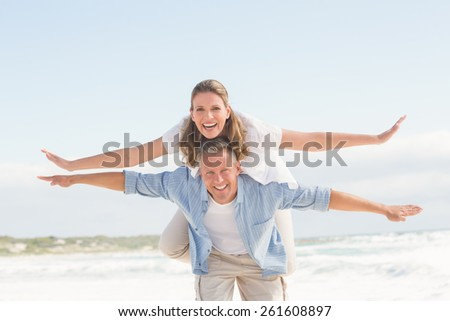 Happy couple having fun together at the beach - stock photo