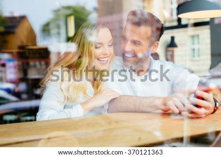 Happy couple having good time at coffee shop browsing internet on smartphone - stock photo