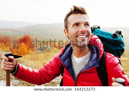 Happy couple hiking with backpacs and sticks in mountains - stock photo