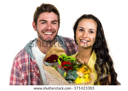 Happy couple holding bouquet and smiling at the camera on white screen - stock photo