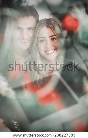 Happy couple holding each other against instant photos on wooden floor - stock photo