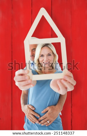 Happy couple holding house outline against red wooden planks - stock photo