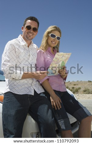 Happy couple holding map - stock photo
