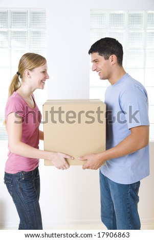 Happy couple holding one cardboard box. They're looking at each other's. Side view. - stock photo