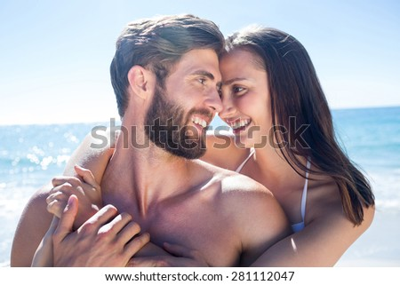 Happy couple hugging and smiling at each other at the beach - stock photo