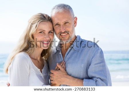 Happy couple hugging each other and looking at camera at the beach - stock photo