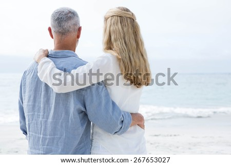 Happy couple hugging each other and looking at the sea at the beach - stock photo