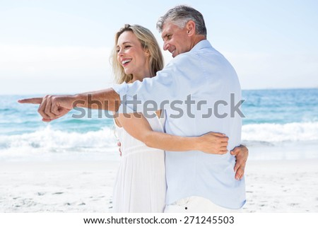 Happy couple hugging each other and pointing something at the beach - stock photo