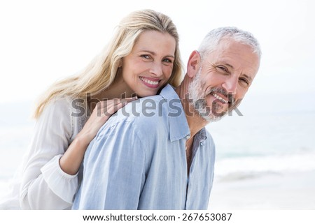 Happy couple hugging each other and smiling at camera at the beach - stock photo