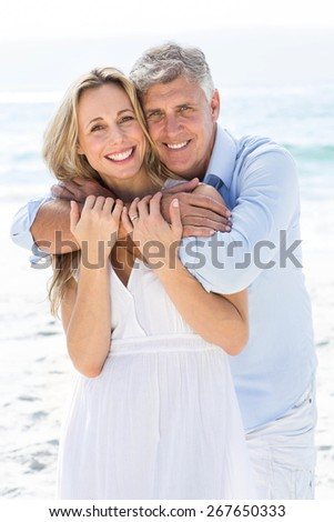 Happy couple hugging each other by the sea at the beach - stock photo
