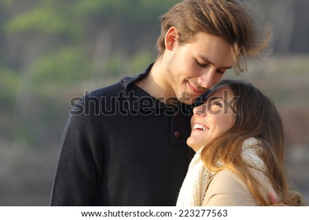 Happy couple hugging in love outdoors at sunset with an unfocused background - stock photo