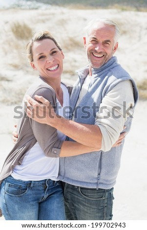 Happy couple hugging on the beach looking at camera on a bright but cool day - stock photo