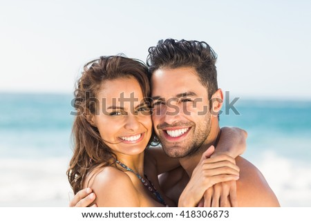 Happy couple hugging on the beach on a sunny day - stock photo