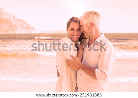 Happy couple hugging on the beach woman looking at camera on a sunny day - stock photo