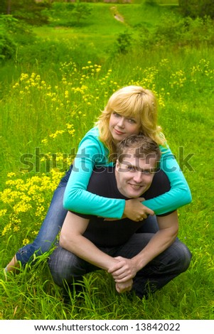 Happy couple hugging on the grass - stock photo