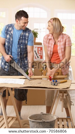 Happy couple improving new house, working together at table.? - stock photo