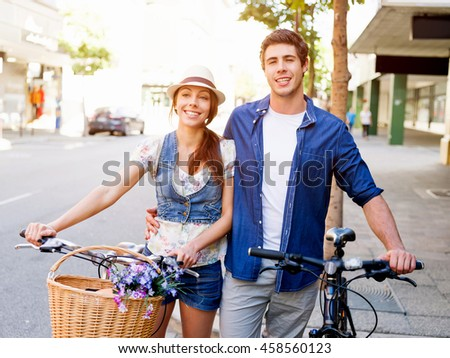 Happy couple in city with bike - stock photo