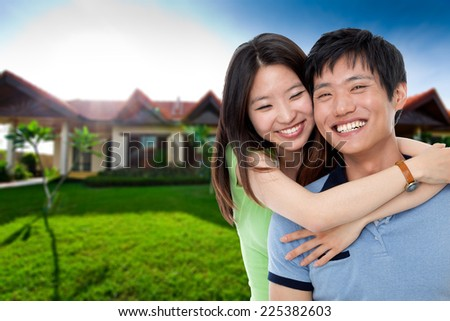 Happy couple in front of their house - stock photo