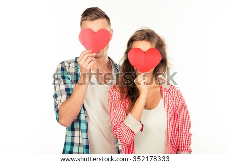 Happy couple in love embracing each other hiding faces behind two paper hearts - stock photo