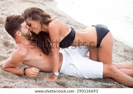 Happy Couple in love having fun on beautiful evening tropical beach.Handsome man holding his sexy girlfriend on hands.Laughing and having fun on the beach,Couple in love hugging and kissing.vacation - stock photo