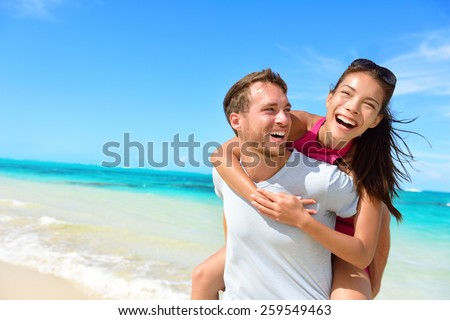 Happy couple in love on beach summer vacations. Joyful Asian girl piggybacking on young Caucasian boyfriend playing and having fun in sunny tropical destination for travel holiday. - stock photo