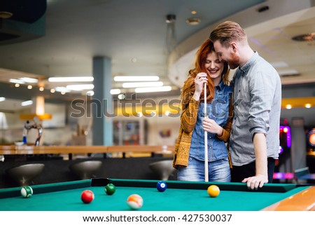 Happy couple in love playing snooker - stock photo