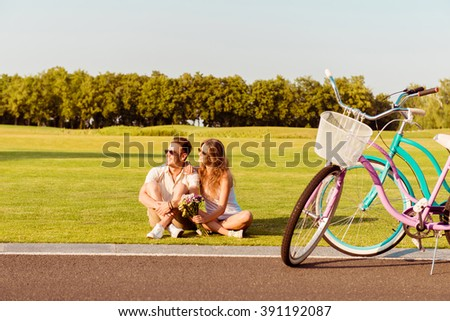Happy couple in love sitting on the grass near their bicycles - stock photo