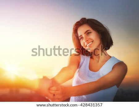 Happy couple in love. Stunning sensual portrait of young stylish fashion couple outdoors. Young woman holds the hand of her boyfriend on background sunset sky. - stock photo