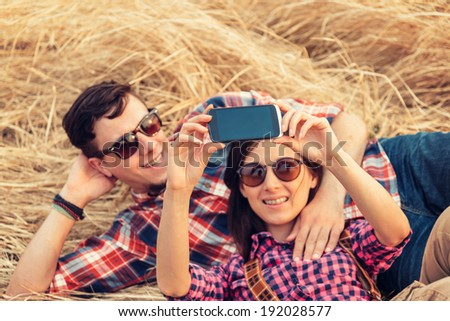 Happy couple in love takes photographs self portrait with camera phone - stock photo