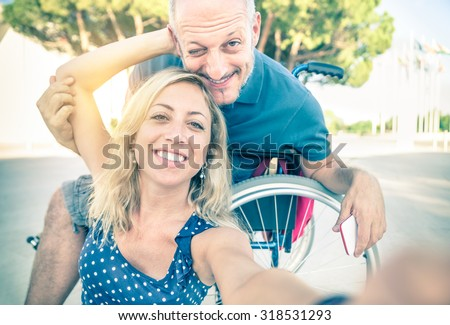 Happy couple in love taking selfie in urban city background - Disability positive concept with man on wheelchair - Vintage filtered look with soft focus on smiling woman due du sun flare halo - stock photo
