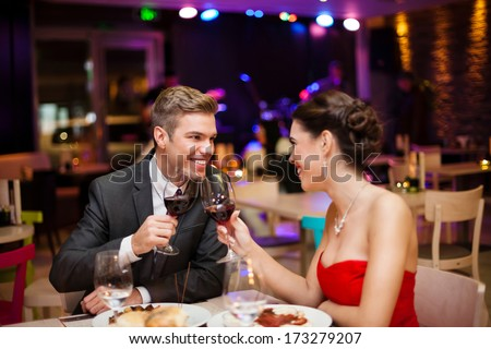 happy couple in restaurant looking each other and toasting - stock photo