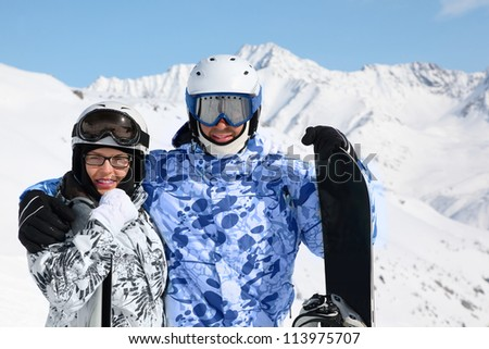 Happy couple in sport suits and helmets stand with snowboard and skis on mountain. - stock photo