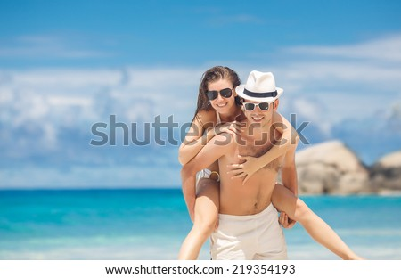 Happy couple in sunglasses piggybacking cheerful on tropical beach during summer holidays vacation. couple in love having fun on tropical ocean Seychelles beach. Maldives. Hawaii beach - stock photo