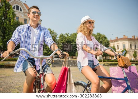 Happy couple in sunglasses with shopping bags riding on bicycles on the city street. - stock photo
