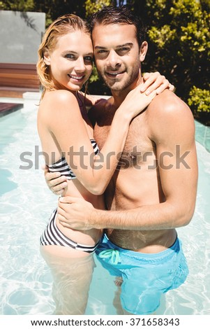 Happy couple in the pool embracing and looking at the camera - stock photo
