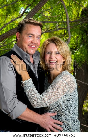 Happy couple in their 40s celebrating their anniversary with an outdoor portrait. - stock photo