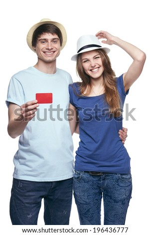 Happy couple in tshirts and straw hats hugging, man showing blank credit card, on white background - stock photo