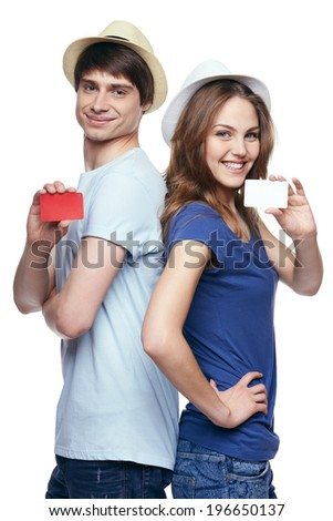 Happy couple in tshirts and straw hats standing back to back, showing blank credit cards, on white background - stock photo