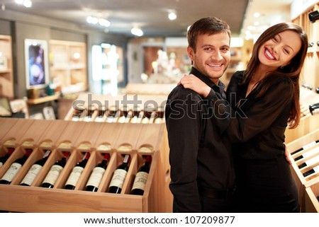 Happy couple in wine shop - stock photo
