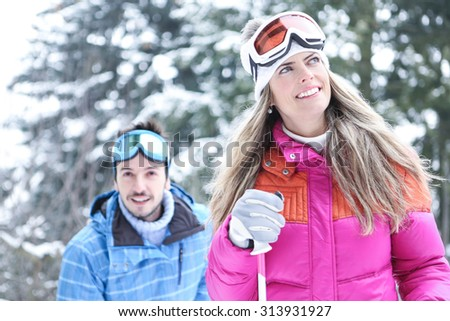 Happy couple in winter skiing together through snow - stock photo
