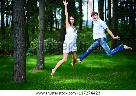 Happy couple jumping high of joy in park - stock photo
