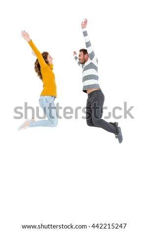 Happy couple jumping in excited on white background - stock photo