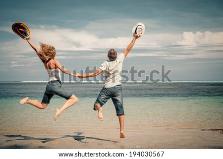 happy couple jumping on the beach at the day time - stock photo