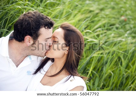 Happy couple kissing in nature - stock photo