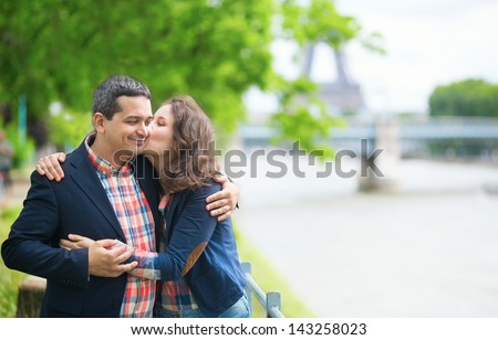 Happy couple kissing near the Seine - stock photo