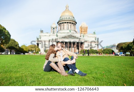 Happy couple kissing on a grass in Saint-Petersburg - stock photo