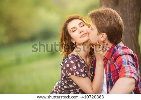 Happy couple kissing on a green meadow  - stock photo