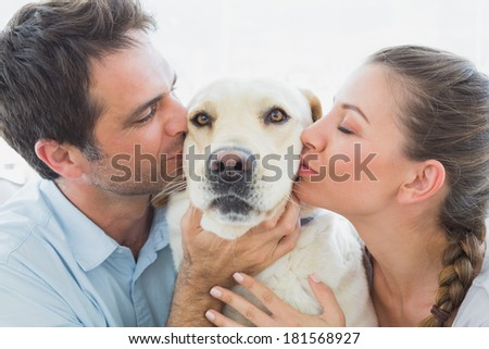 Happy couple kissing their yellow labrador on the couch at home in the living room - stock photo