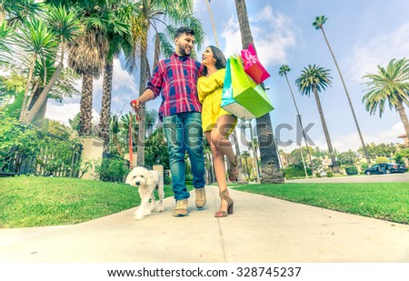 Happy couple laughing and walking while shopping - Boyfriend with poodle embracing his beautiful girlfriend walking on Beverly Hills - Rich persons having fun - stock photo